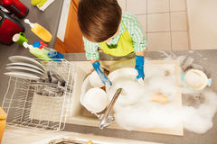 Boy rinsing dishes in the sink full of soap suds. Top view portrait of of kid boy rinsing dishes under running water in the sink full of soap suds Royalty Free Stock Image
