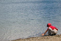 Boy and river. A boy sitting at the river Royalty Free Stock Image