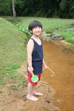 Boy at the river. Boy holding fishing rod standing by the river Stock Image