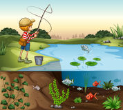 Boy on the river bank fishing alone Stock Image