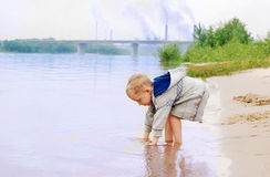 Boy on the river coast near plant Royalty Free Stock Images