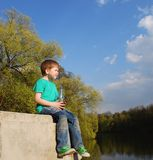 The boy on the river drinking water. From a plastic bottle Royalty Free Stock Images