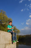 The boy on the river drinking water. From a plastic bottle Stock Photo
