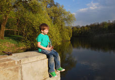 The boy on the river drinking water. From a plastic bottle Royalty Free Stock Photography