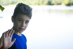 Boy on the riverbank giving the hand signal royalty free stock images