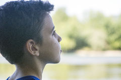 Boy on the riverbank Stock Photography