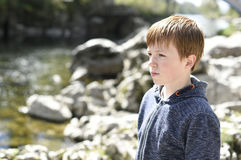 Boy by the riverside. Young boy, looking out over the water from the riverside stock photo