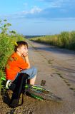 The boy on road. The boy with a bicycle on long road Royalty Free Stock Photos