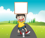 A boy at the road holding an empty signage Stock Photo