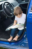 Boy with road map sits in car Royalty Free Stock Image