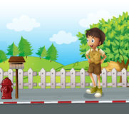 A boy at the road near the wooden mailbox Stock Images