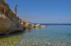 The boy on the rock. The boy on the rock in sea. Marathias beach, Zakynthos Island, Greece stock photos