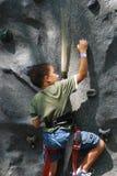 Boy rock climbing. Details of a young boy rock climbing on a vertical wall Royalty Free Stock Photo