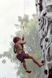 Boy Rock Climbing, Jakarta Indonesia. Boy climbs a rock wall in an amusement park, Jakarta, Indonesia royalty free stock photos