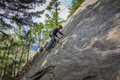 Boy Rock Climbing Outdoors. Young boy climbing rock face in the Adirondack Mountains of Upstate New York Royalty Free Stock Photography