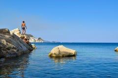 The boy on the rock. The boy on the rock in sea. Marathias beach, Zakynthos Island, Greece royalty free stock photos