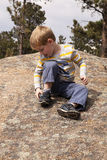 Boy with rock in shoe Stock Photo