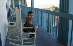 Boy on rocking chair. Cute smiling young boy on a blue rocking chair at the Inn Royalty Free Stock Photography