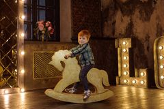 Boy on a rocking horse. Red-haired boy on a rocking chair.nPhotoshoot in the studio in the style of a fairytale photo.nVintage photo shoot Stock Photo