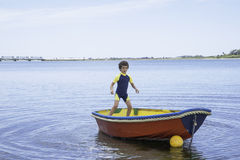 Boy rocking small boat Stock Photography