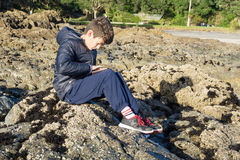Boy on rocks with mobile device Waipu Cove Royalty Free Stock Image