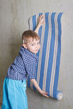 Boy with roll of wallpaper near wall stock photo