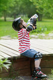 Boy on roller skates drinks water Royalty Free Stock Photography