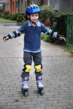 Boy with rollerblades. Young boy exercises  with rollerblades. He is good protected with helmet and pads for knees and elbows Royalty Free Stock Photo