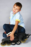 Boy in rollerblades sitting Stock Image
