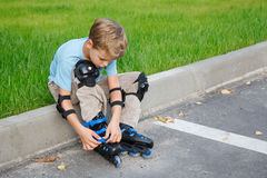 Boy with rollerblades sitting on edge of road. Stock Images