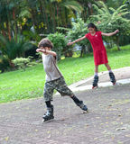 Boy rollerblading with his sister Royalty Free Stock Images