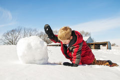 Boy rolling snow for snowman. Young child rolls a giant snowball to make a snowman. Country setting Stock Photo
