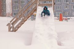 Boy rolls down a snowy wooden slide during a snowfall. stock image