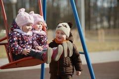 Boy rolls girls on swings Stock Photos