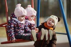 Boy rolls girls on swings Royalty Free Stock Photography