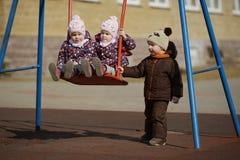 Boy rolls girls on swings Royalty Free Stock Images