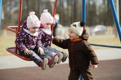 Boy rolls girls on swings Royalty Free Stock Image