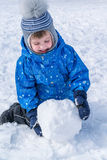 The boy rolls a snowball. A snowball for a snowman. Royalty Free Stock Images