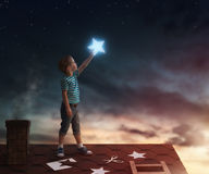 Boy on the roof. Fairy tale! The child hanging the stars in the sky. Boy on the roof cuts out stars Stock Photo