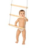 Boy with a rope-ladder 3. A little boy trying to climb a rope-ladder Stock Photos