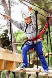 Boy on the rope track in safe equipment Stock Photo