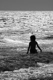 Boy in rough surf at the beach in black and white Royalty Free Stock Photo