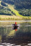 Boy in a rowing boat on a mountain lake. Royalty Free Stock Photo
