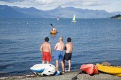 Boy rowing in a canoe. Three men watching a boy rowing in a canoe Stock Image