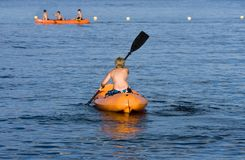 Boy rowing in a canoe. A boy rowing in a canoe towards his friends in a lake Stock Images
