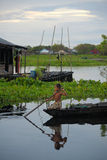 Boy rowing in a floating village on the Tonle Sap Lake Cambodia Royalty Free Stock Images