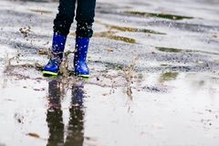 Boy in rubber blue rainboots jumping to dirty puddle Stock Photos