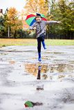Boy in rubber blue rainboots jumping to dirty puddle. Happy little boy in rubber blue rainboots jumping to dirty puddle. Rainy autumn day Royalty Free Stock Photography