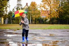 Boy in rubber blue rainboots jumping to dirty puddle. Happy little boy in rubber blue rainboots jumping to dirty puddle. Rainy autumn day Stock Image