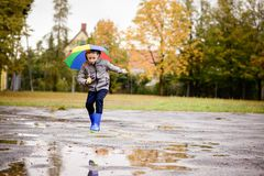 Boy in rubber blue rainboots jumping to dirty puddle Stock Image